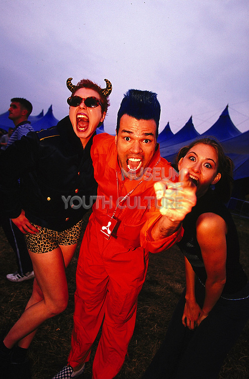 Man with blue hair wearing an orange boiler suit woman wearing hot pants and and devil horns Creamfields 2000