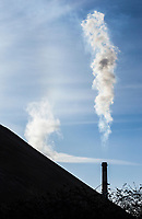 A smoke stack discharging smoke or steam in south Seattle, Washington,  USA