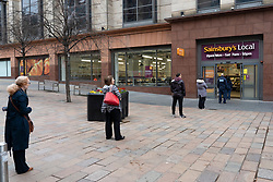Glasgow, Scotland, UK. 26 March, 2020. Views from city centre in Glasgow on Thursday during the third day of the Government sanctioned Covid-19 lockdown. The city is largely deserted. Only food and convenience stores open. Pictured; Customers queue using social distancing to enter Sainsbury's Local supermarket on a one in one out basis. Iain Masterton/Alamy Live News