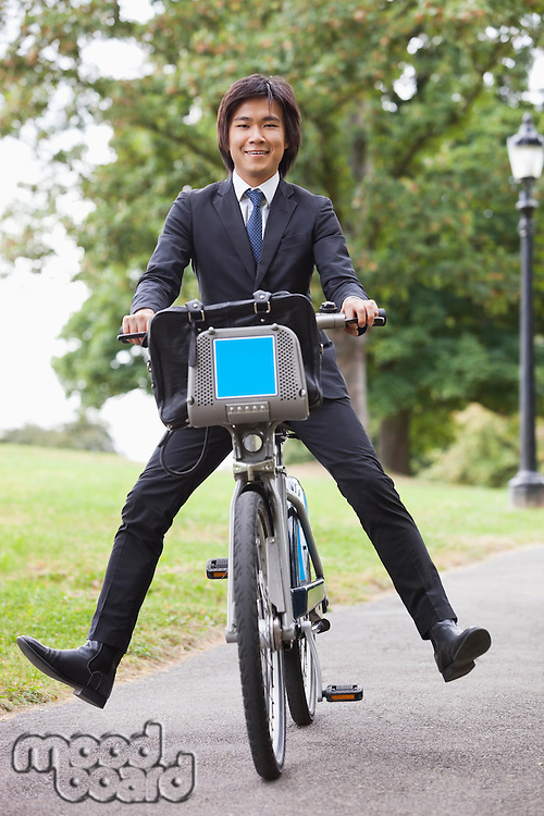 Portrait of young businessman riding bicycle with apart