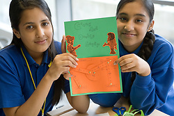 Two Asian school girls in Technology class holding up their project on Crank and lever mechanisms,