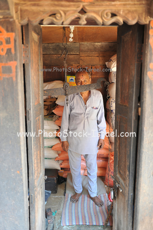 Asia, Nepal, Kathmandu, Man in his shop. Primitive scale in the foreground and bags of rice in the background