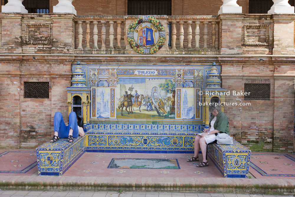 Tourists sit by tiled mural (azulejo) of Toledo province, in Plaza de Espana in Seville. The Plaza mainly consists of Government buildings, the city's Town Hall, with sensitive adaptive redesign, is located within it. The Plaza's tiled 'Alcoves of the Provinces' are backdrops for visitors portrait photographs, taken in their own home province's alcove. This semicircular enclosure was built by Aníbal González, the great architect of Sevillian regionalism, for the Ibero-American exposition held in 1929. It is a landmark example of the Renaissance Revival style in Spanish architecture.