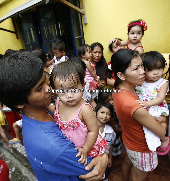 60915392<br /> Parents and their children line up outside a community health centre as they wait for their measles vaccine in Caloocan City, the Philippines, Jan. 13, 2014. Health centres in Metro Manila have been giving first dose of measles vaccines to children as part of the Philippine Department of Health s (DOH) heightened campaign to prevent the spread of measles in the National Capital Region after recording a total of 1,724 measles cases from Jan. 1 to Dec. 14 last year,  Monday, 13th January 2014. Picture by  imago / i-Images<br /> UK ONLY