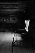 "Black and white image of a steel bed frame and springs in old, empty, rustic log cabin with ""Rachel"" written on the back wall."