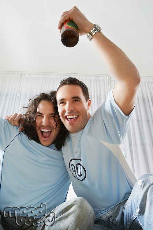 Two men watching television and cheering with beer bottle