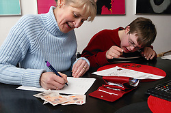 Single parent writing a list while her son counts out money,