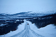 Car travels through arctic wilderness at nightfall by Kilpisjarvi on route from Finland into Norway