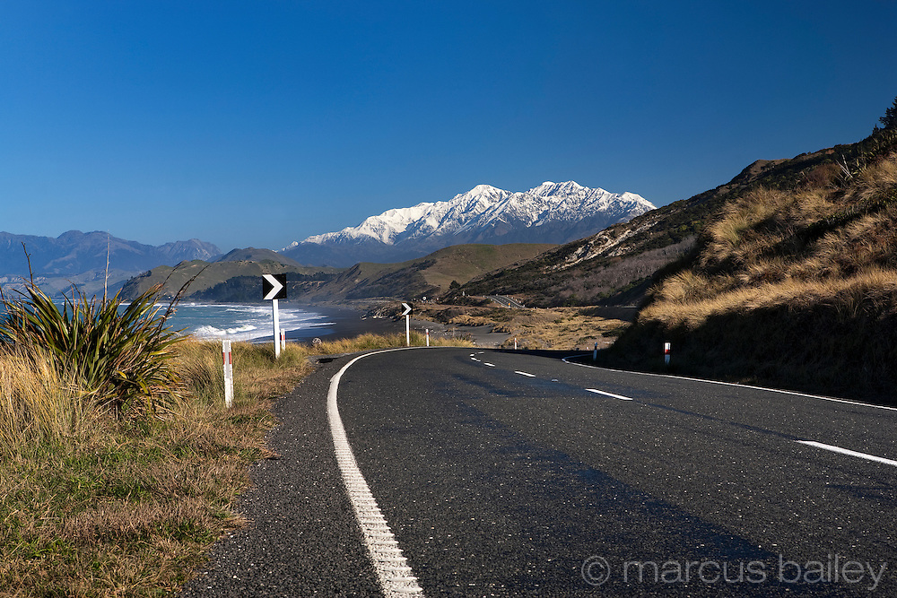 scenic road beside nz coast, with snow capped mountains, kaikoura coast, marlborough, new zealand