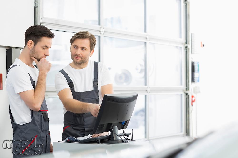 Male automobile mechanics conversing in repair shop
