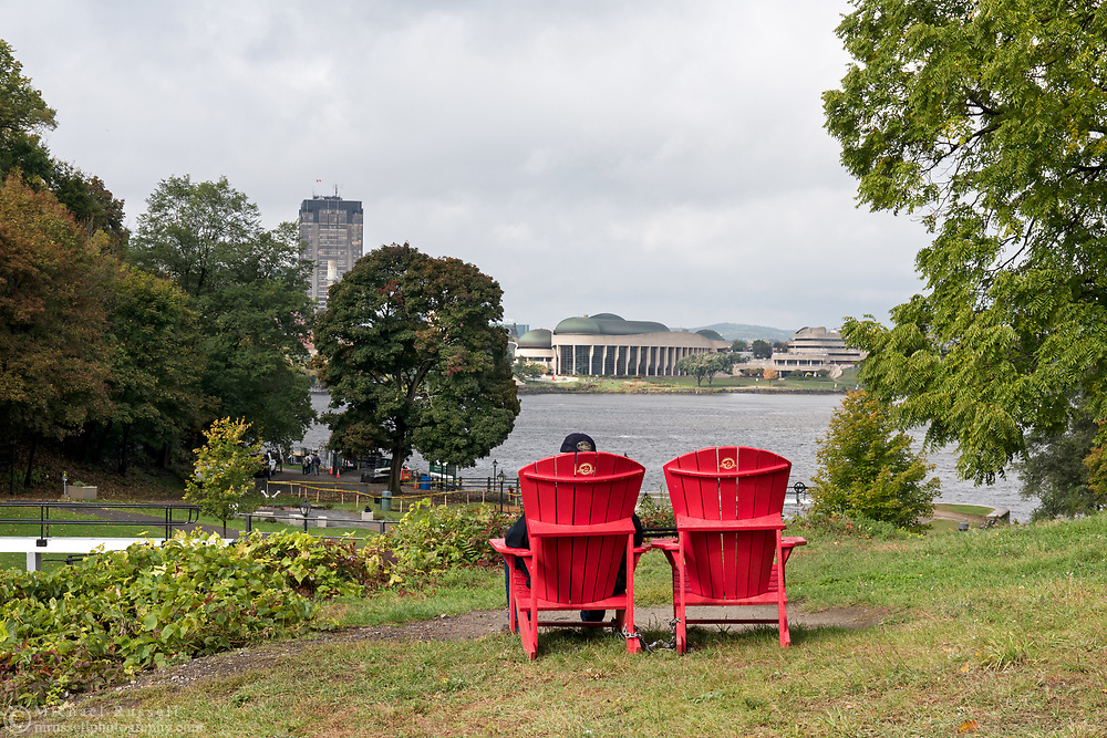 Adirondack chairs with a view of the Ottawa River and the Canadian Museum of History (Museum of Civilization) in Gatineau Qu&eacute;bec.<br /> Photographed next to Ottawa Locks 1-8 on the Rideau Canal in Ottawa, Ontario, Canada.
