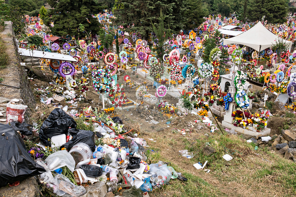 A pile of trash sits near hundreds of hillside graves decorated with flowers and wreaths for the Day of the Dead festival November 3, 2017 in Nuevo San Juan Parangaricutiro, Michoacan, Mexico.