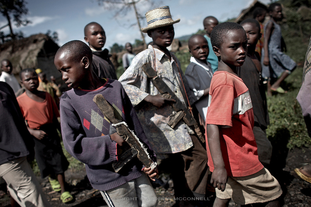 Young boys carry wooden guns through the streets of Kichanga, North Kivu, DRC.