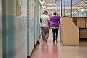 A volunteer and a prisoner walk down  on E wing. HMP Wandsworth, London, United Kingdom