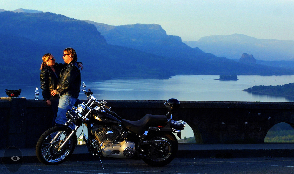 Robert Clausen and Vicki Jo Stebner take in the sunset and view from Crown Point along the Columbia River east of Portland, Oregon. The scenic highway road is popular with motorcyclists and bicyclists due to the dramatic views and curvy roads.