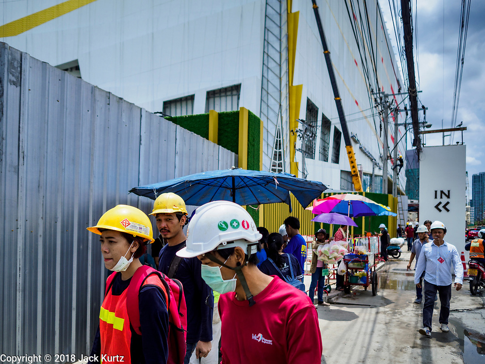 17 SEPTEMBER 2018 - BANGKOK, THAILAND: Construction workers from the ICONSIAM construction site walk along Chareon Nakhon Road in Thonburi. ICONSIAM is a mixed-use development on the Thonburi side of the Chao Phraya River. It is expected to open in 2018 and will include two large malls, with more than 520,000 square meters of retail space, an amusement park, two residential towers and a riverside park. It is the first large scale high end development on the Thonburi side of the river and will feature the first Apple Store in Thailand and the first Takashimaya department store in Thailand.   PHOTO BY JACK KURTZ