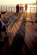 Long shadows cast as sun goes down beyond pier, 1990s