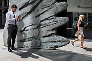 A financial industry businessman checks messages as a lady walks the other side of the sculpture entitled City Wing on Threadneedle Street in the City of London, the capital's financial district (aka the Square Mile), on 11th July 2019, in London, England. City Wing is by the artist Christopher Le Brun. The ten-metre-tall bronze sculpture is by President of the Royal Academy of Arts, Christopher Le Brun, commissioned by Hammerson in 2009. It is called 'The City Wing' and has been cast by Morris Singer Art Founders, reputedly the oldest fine art foundry in the world.