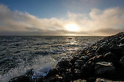 Waves break on the rocks as the sun sets over the San Francisco bay from  César Chávez Park at the Berkeley Marina in Berkeley, California (Photo by Brian Garfinkel)
