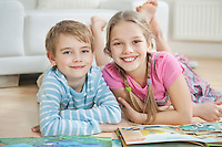 Portrait of happy brother and sister with story books while lying on floor
