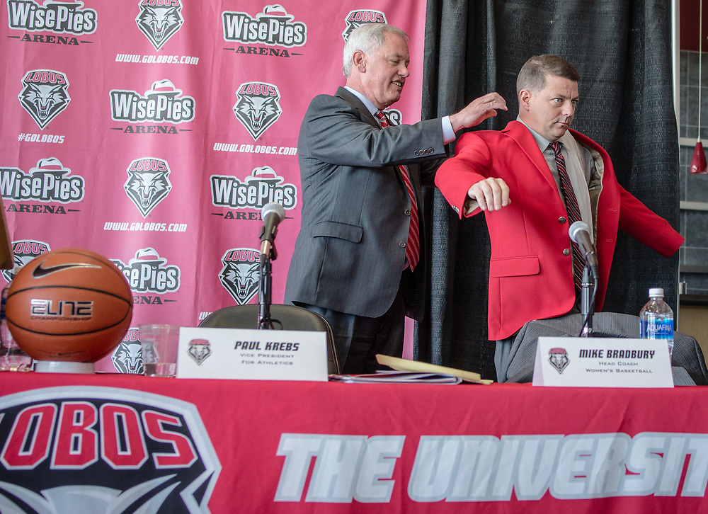 03.31.16/ UNM's vice president for Athletics Paul Krebs (Cq), left, puts on the Cherry jacket on newly hired women basketball coach Mike Bradbury (Cq) during a press conference Thursday afternoon during a press conference at the Pit.  Albuquerque, New Mexico(Roberto E. Rosales/Journal