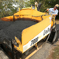 Adam Robison | BUY AT PHOTOS.DJOURNAL.COM<br /> John Robbins, job foreman for Lee County, helps re-pave the walking tracj at Saltillo City Park on Monday.