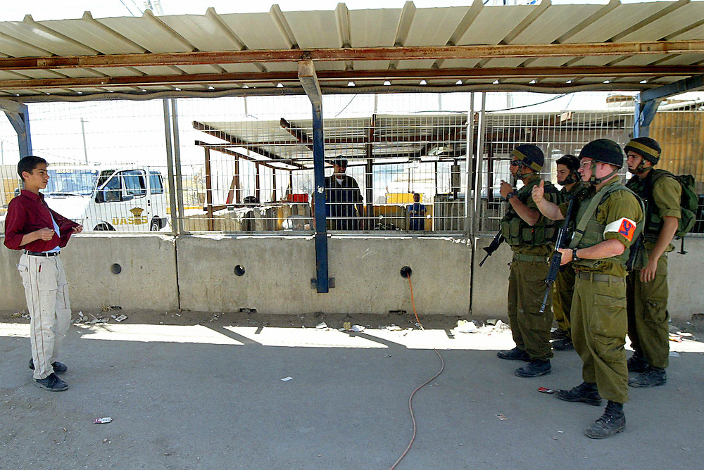 A Palestinian youth is asked to open his shirt during a control  at the Qualandia checkpoint...Photo by Olivier Fitoussi