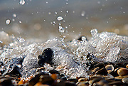Wavelets breaking and splattering on pebbles on the sea shore