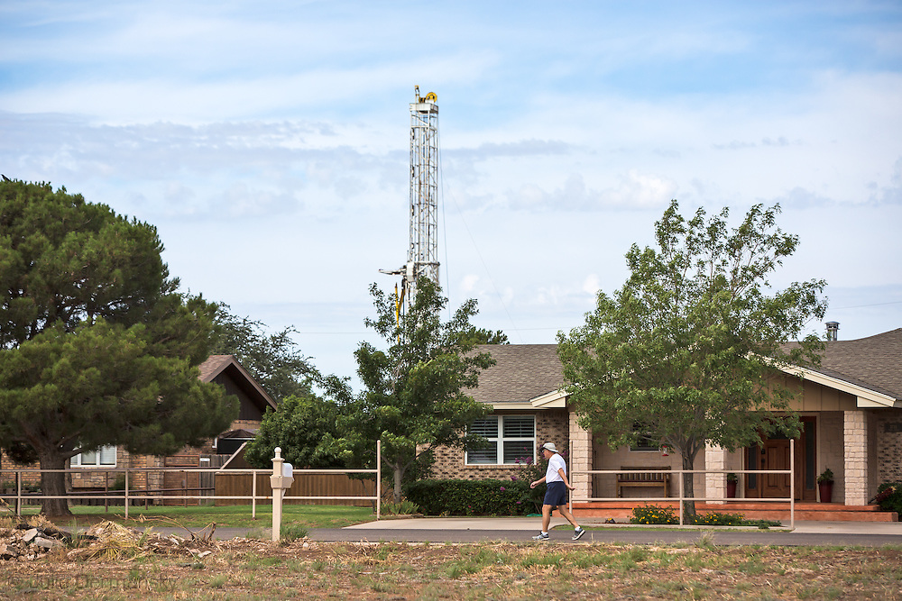 Man walking by a home in Midland, Texas across from a Hydraulic fracturing drilling rig. Midland Texas is part of the  Permian Basin. The fracking industry recently revived production and the area is experiencing a new oil boom.