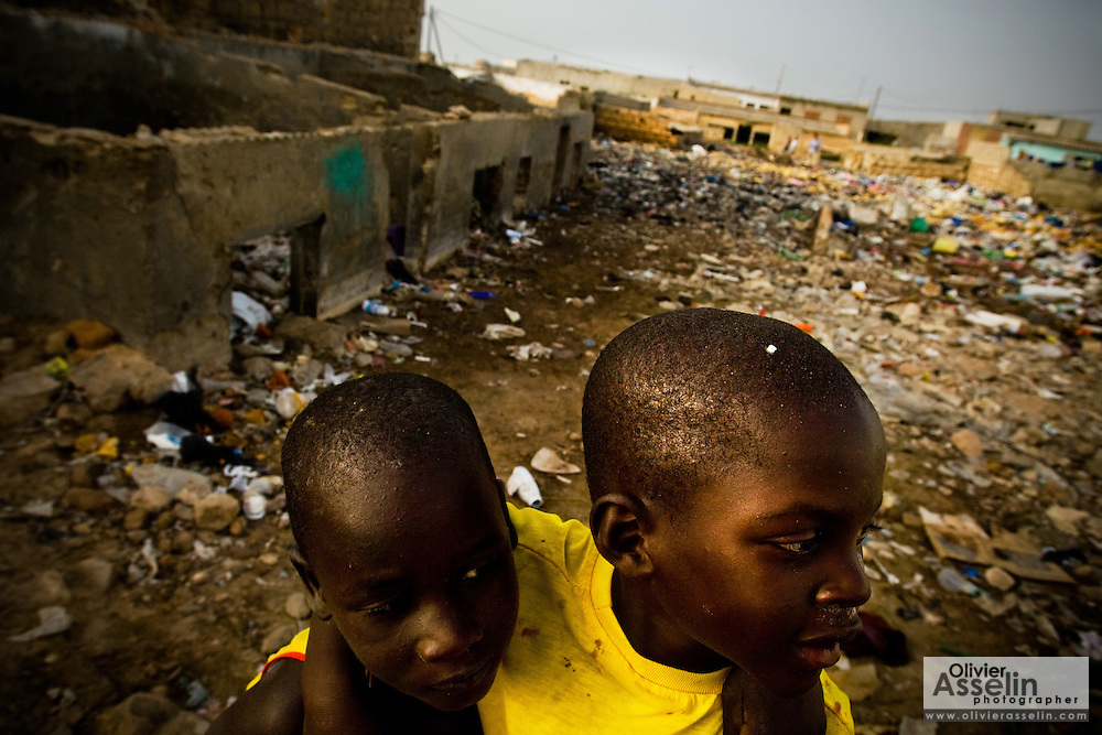Boys play in a trash covered field between decrepit homes that are buried halfway in garbage and dirt in the Medina Gounass neighborhood of Guediawaye, Senegal on Thursday April 30, 2009.(Olivier Asselin for the New York Times).