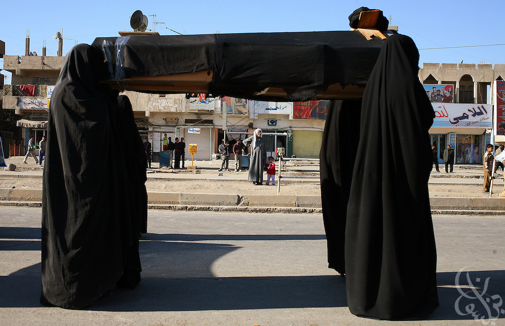 Shia women loyal to cleric Moqtada al-Sadr carry a symbolic coffin during a November 28, 2006 parade commemorating the 7th anniversary of the death of Moqtada's father, Mohammed Sadiq al-Sadr in the Sadr City district of Baghdad, Iraq. The elder al-Sadr and two of his sons, Mustafa, and Mu'ammal were killed in 1999 as they drove through the holy city of Najaf.