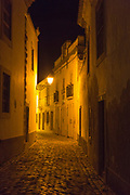 Narrow alleyway illuminated by glow of orange streetlight in the medieval old town, Cidade Velha, city of Faro, Portugal, Europe,