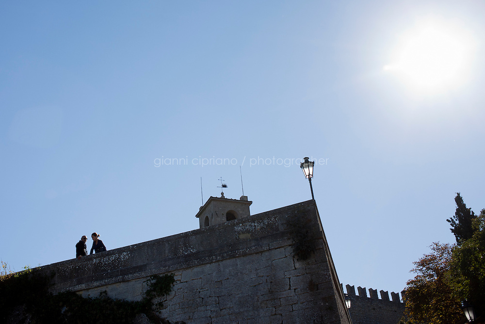 SAN MARINO, SAN MARNO - 3 OCTOBER 2011: A man and a woman watch the view of the Adiatic Sea from the Prima Torre (First Tower)  in San Marino, San Marino on October 3, 2011. The San Marino national football team is the last team in the FIFA  World Ranking (position 203). San Marino, whose population reaches 30,000 people, has never won a game since the team was founded in 1988. They have only ever won one game, beating Liechtenstein 1&ndash;0 in a friendly match on 28 April 2004. The Republic of San Marino, an enclave surronded by Italy situated on the eastern side of the Apennine Moutanins, is the oldest consitutional republic of the world<br /> <br /> <br /> ph. Gianni Cipriano