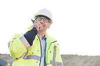 Happy supervisor using walkie-talkie at construction site against clear sky