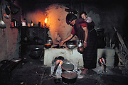 Sangay cooks at the wood-burning hearth and earthen stove in the kitchen of the rammed earth home she and her husband and children share with Sangay's parents, and brothers and sisters. Shingkhey Village, Bhutan. Nalim and her daughter Sangay care for the children and work in their mustard, rice, and wheat fields. Namgay, who has a hunched back and a clubfoot, grinds grain for neighbors with a small mill his family purchased from the government. From Peter Menzel's Material World Project.