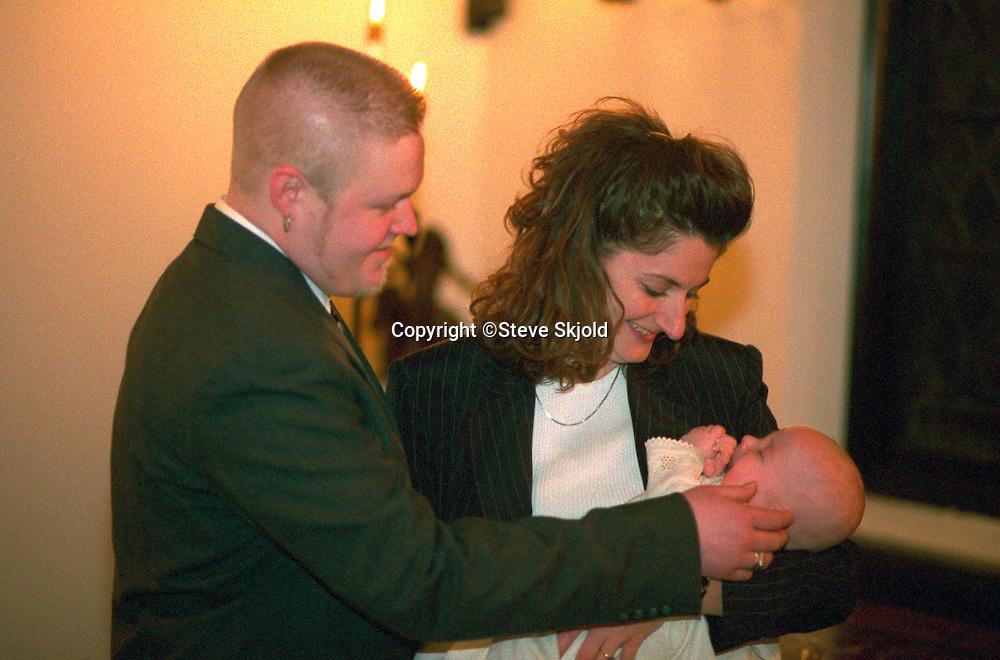 Uncle and aunt godparents holding newly baptized nephew.  St Paul  Minnesota USA