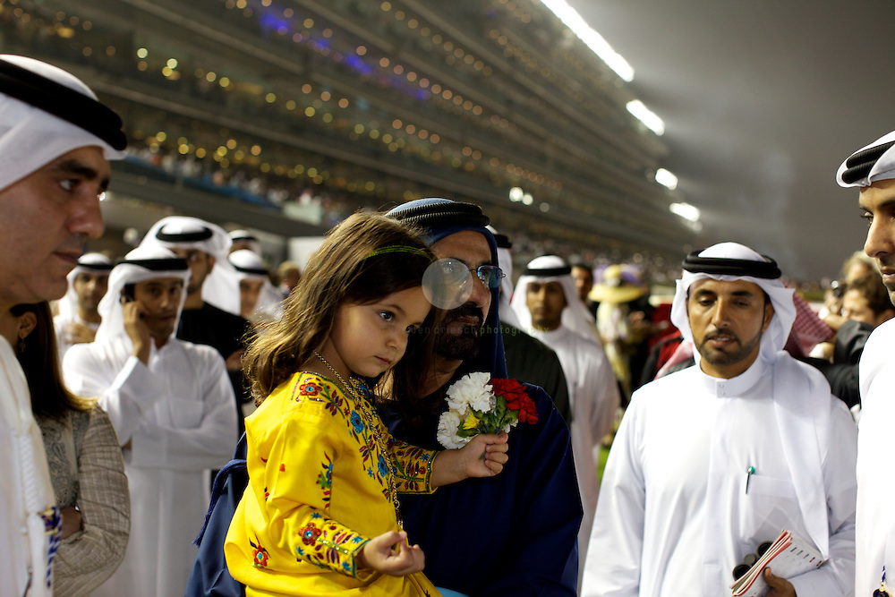 Dubai World Cup 2011. ASIA, UNITED ARAB EMIRATES, EMIRATE DUBAI, DUBAI, 26.03.2011: The Dubai World Cup, the final event of a racing season that run from November till March, is the top sport and society event in Dubai. With prize-money of more than  $US26.00 million it is the highest-paid racing event in the world - anything else would have been a major surprise in this city of superlatives. Event he economic crisis hasn't slowed down the ruler srive for superlative: the price-money for the final race, the Dubai World Cup card, has gone up from $US6.00 in 2009 to $USD10.00 Mio this year. And yet, it is one of the most democratic international sport events that one can attend. While most of the westerners simply want to have a good party (and to get drunk), the ruler's focus is exclusively on the outcome of the races. Large sections of the  crowd- many of them from the Subcontinent and from Africa- simply enjoy a good day out with friends or family. A child watches while her father takes a pre-race afternoon nap. Sheikh Mohamed, the ruler of Dubai, with his daughter.