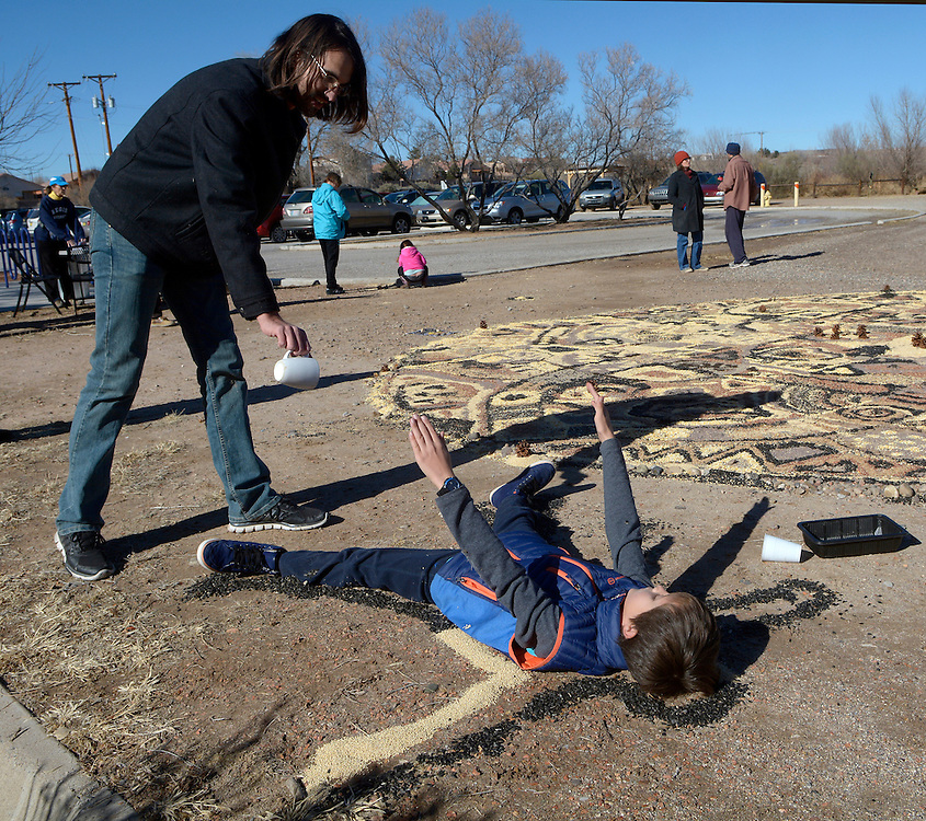 gbs121816k/ASEC -- Hagan Smith, 9,  of Albuquerque, lifts his arms as his father Mike Smith finishes pouring an outline of seeds around him during the creation of the Winter Solstice Seed Mandala at the Open Space Visitor Center on Sunday, December 18, 2016. The community art project is a way to feed the birds at the center.(Greg Sorber/Albuquerque Journal)