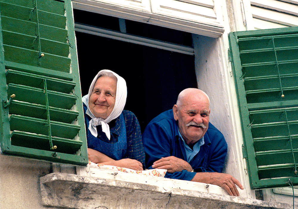 A contented couple greet friends from their shuttered window near Vienna in Austria.