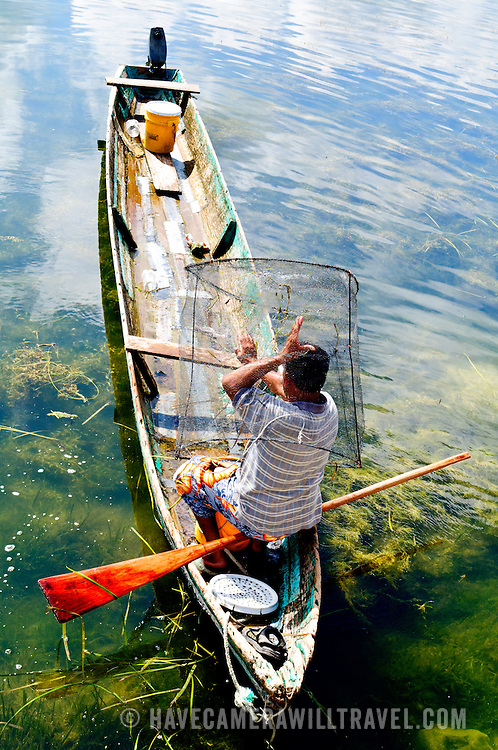 A fishermen tips up a wire basket to tip out the small fish that had been caught along the waterfront of Flores in north Guatemala in Lake Peten Itza.