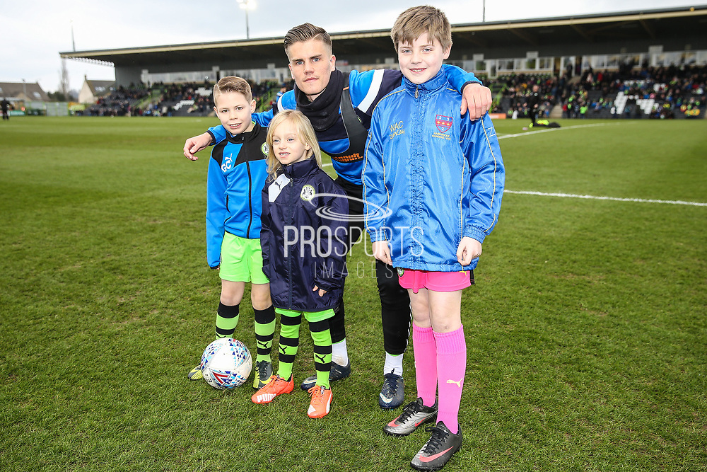 Forest Green Rovers Charlie Cooper(15) with mascots during the EFL Sky Bet League 2 match between Forest Green Rovers and Mansfield Town at the New Lawn, Forest Green, United Kingdom on 24 March 2018. Picture by Shane Healey.