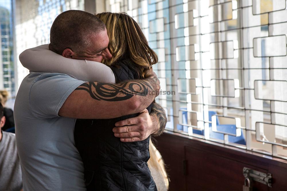 A prisoner embraces his wife at the start of a visit. HMP/YOI Portland, Dorset, United Kingdom.
