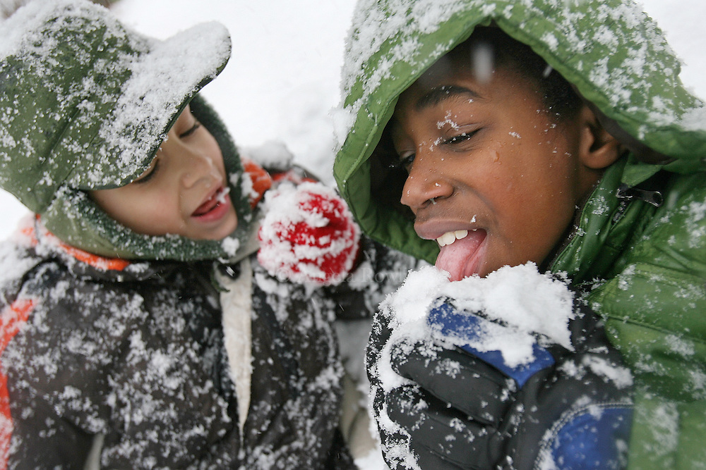 Brothers Sam, 7, left and Devin Neely-O'Donoghue, 9, take a break from shoveling to eat snow in Jamaica Plain, Sunday,  December 21, 2008.