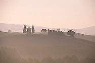 The Chapel Vitaleta and cypress trees surrounded by morning mist in Val d'Orcia, Tuscany, Italy
