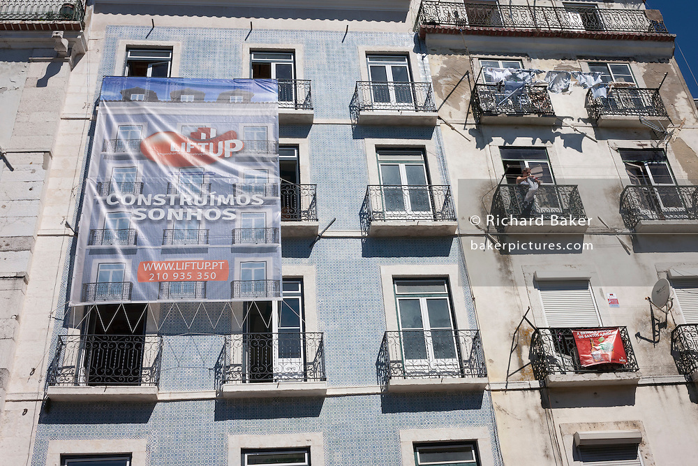 Construction banner hangs from a balcony of a restored apartment building in Lisbon, Portugal.
