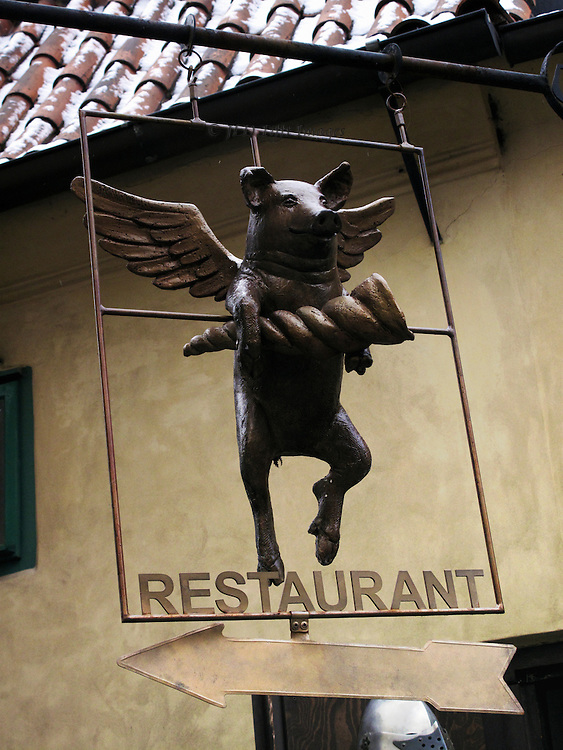 Restaurant sign on Golden Lane, Hradcany Castle, Prague.   Shows a winged pig grinning and holding a twisted horn.