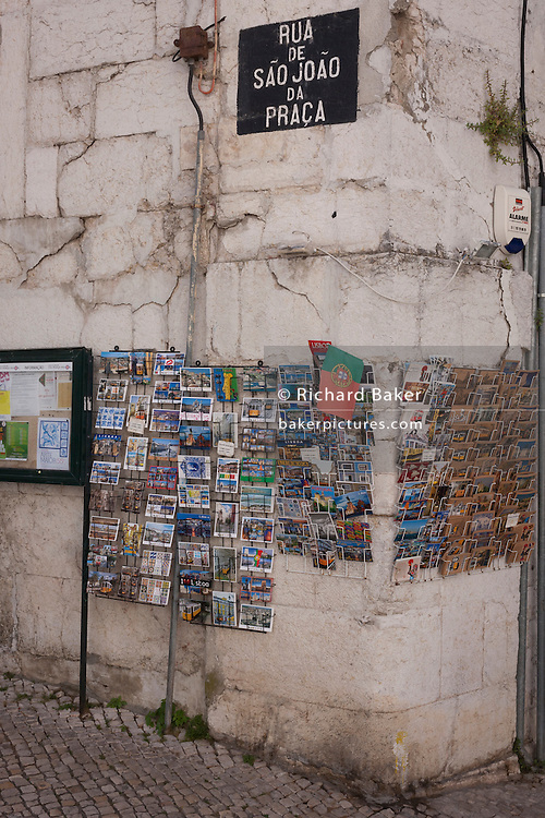"""Postcards are displayed on racks, on Rua de Sao Joao da Praca, a corner in the medieval district of Alfama, on 11th July, in Lisbon, Portugal. The national flag makes an appearance too, the day after Portugal won the final against France in the Euro 2016 football tournament. Alfama partly has its roots from Moorish influences and is the oldest district of Lisbon. Its name comes from the Arabic Al-hamma but could also be derived from the Arabic word Alfamm, meaning the """"mouth"""" in Arabic. (Photo by Richard Baker / In Pictures via Getty Images)"""