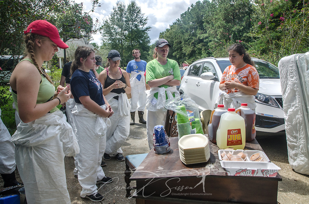 Student volunteers from Louisiana State University's Baptist Collegiate Ministry and other college ministries, pray before eating lunch, Sept. 3, 2016, at a flood-damaged home in Denham Springs, La. The students were among 450 from six states who gathered in Baton Rouge and nearby communities on Labor Day weekend to help survivors of the mid-August flood. (Photo by Carmen K. Sisson)
