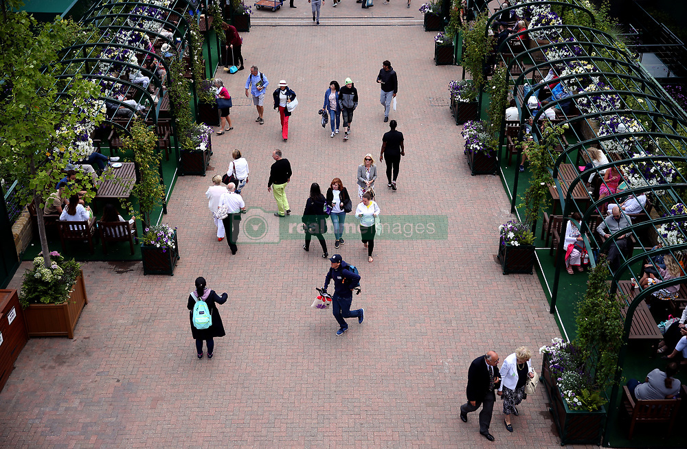 Spectators make their way around the grounds on day nine of the Wimbledon Championships at The All England Lawn Tennis and Croquet Club, Wimbledon.