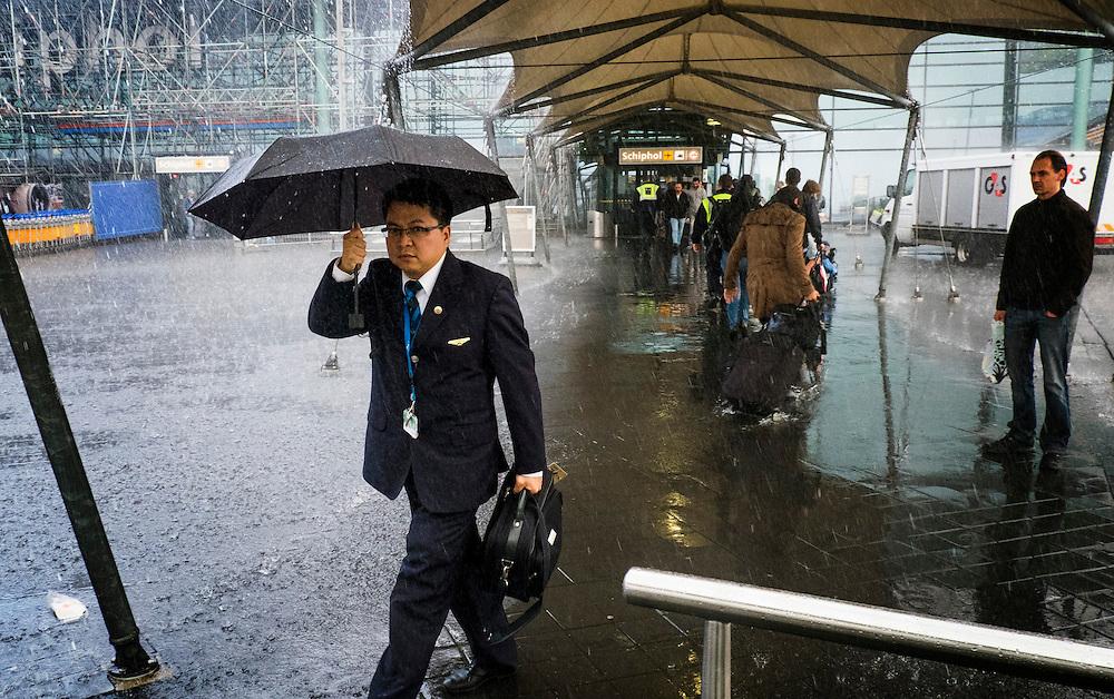 Nederland, Schiphol, 11 sept  2013<br /> Felle korte regenbui op Schiphol.<br /> Zakenman met paraplu snelt naar de taxi's.<br /> <br /> Foto(c): Michiel Wijnbergh